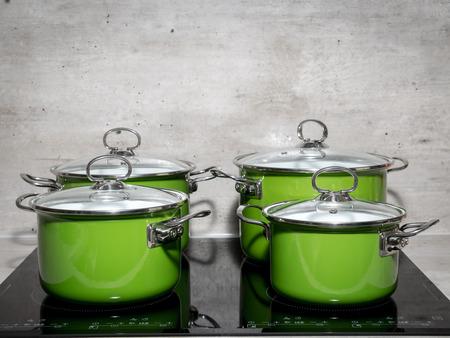ustensiles de cuisine: Quatre émail vert faitouts sur plaque à induction noire Banque d'images