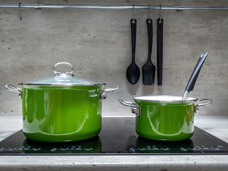 Twee groene emaille stewpots op zwarte inductie kookplaat Stockfoto