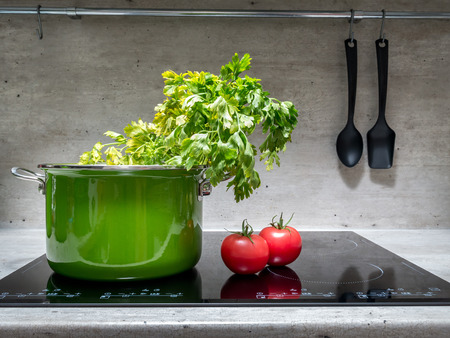 Olla de esmalte verde con perejil y dos tomates en cocina de inducción negro