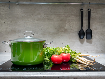 Green enamel stewpot with parsley and two tomatoes on black induction cooker Stock Photo - 43183729