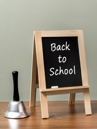 handbell: Silver handbell and blackboard with Back to School phrase placed on brown desktop over green wall