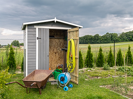 Wooden shed with different garden tools and equipment