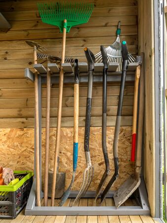 mattock: Wooden rack with different garden tools and equipment