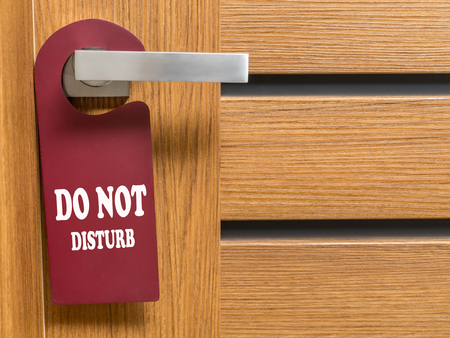 hotel sign: Do Not Disturb door hanger hanging on hotel room door handle