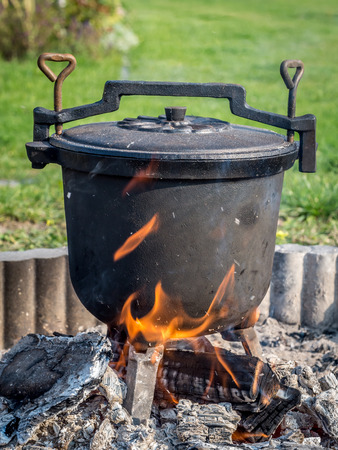 fare: Black cast-iron kettle with fare placed on fire