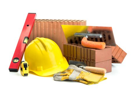 spirit level: Perforated bricks, stainless steel trowel, yellow helmet, protective gloves and spirit level isolated on white
