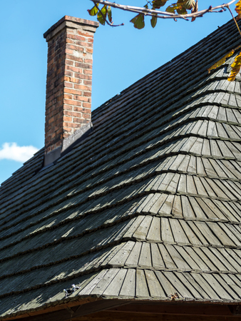 exterior shape: Closeup of wooden shingle roof with brick chimney