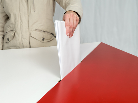 local government: Voter casting a vote into ballot box during election to the Polish Parliament