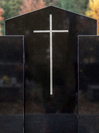 symbolical: Closeup of black granite tombstone with white cross Stock Photo