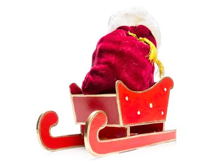 sackful: Santa Claus bag full of christmas presents in red sleigh over white background Stock Photo
