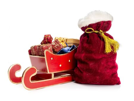 sackful: Red sleigh full of christmas presents and Santa Claus bag over white background