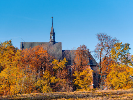 church building: Countryside old catholic church surrounded by trees in fall colors with clear blue sky
