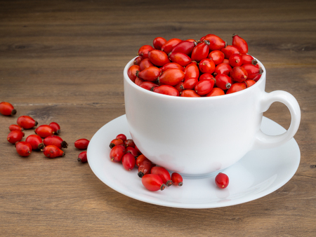 briar: White mug filled with briar fruit on wooden surface