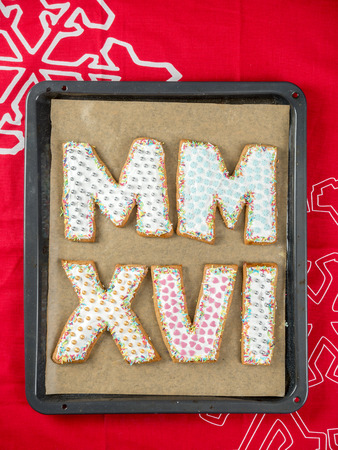 numerals: Home-made gingerbread cookies in shape of Roman numerals representing 2016 New Year date on baking tray
