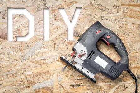 osb: DIY acronym cut out in OSB panel with electric jigsaw