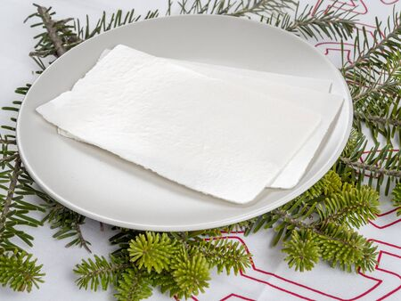 fir twig: Traditional Christmas Eve white wafer on a plate with fir twig