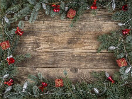 frameworks: Christmas framework arranged from spruce branches and seasonal decorations placed on wooden rustic boards with copy space Stock Photo