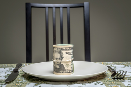corporate greed: Wad of american dollars served on plate with fork and knife placed on table - business concept