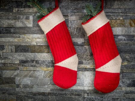 red stone: Pair of red Santa stocking hanging on stone wall