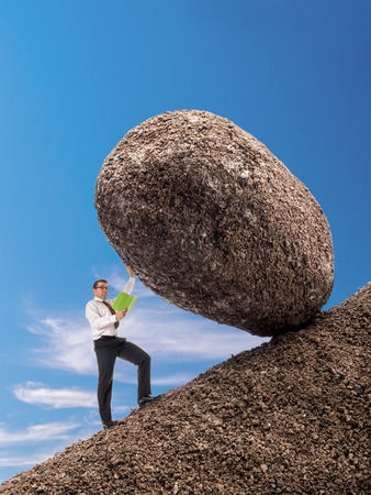 blocking: Businessman reading a book standing on slope blocking easily giant boulder with one hand
