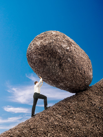 Businessman rolling up giant boulder on slope over blue sky Stockfoto