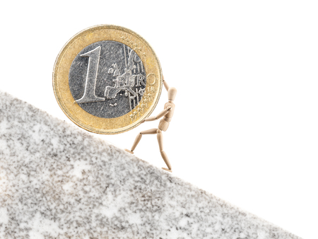 inclined: One Euro coin being rolled uppwards on inclined plane by wooden dummy on white background