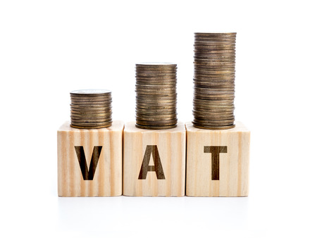 vat: Piles of coins arranged in increased manner placed on wooden block with VAT word