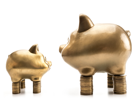 Two big and small golden piggybanks standing opposite each other on piles of money on white background