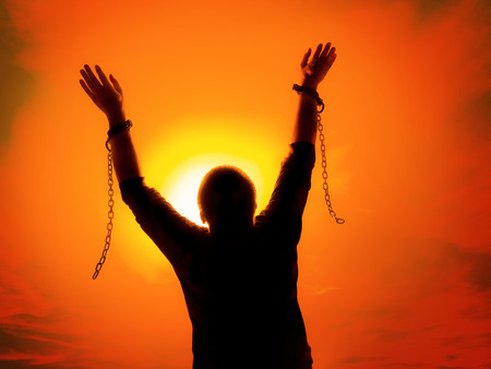 Silhouette of man agains the sunset ssky raising up his hands as he becomes free from chains and shackles