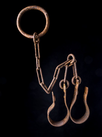 manacles: Old rusty shackles on black background Stock Photo