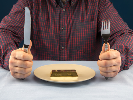 Businessman sitting behind a table with fork and knife ready to eat bar of gold served on plate - business concept
