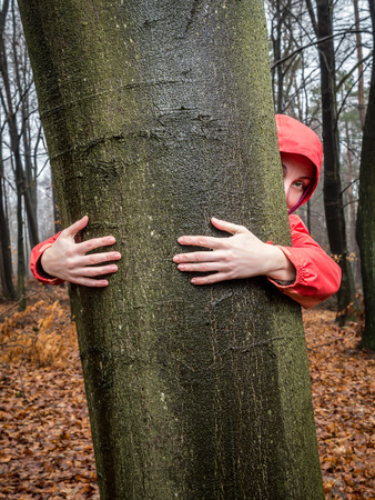 Woman hugging a tree in the forest