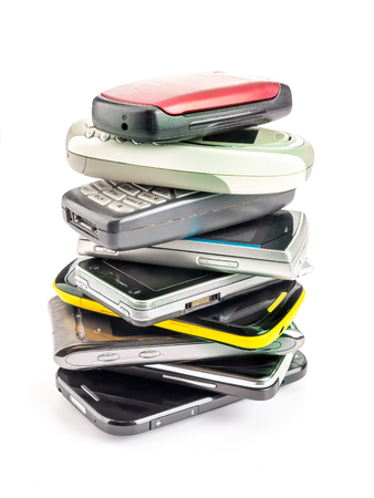 wireless telephone: Pile of old and used mobile phones on white background