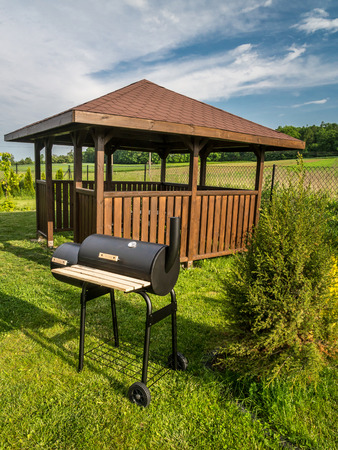 bower: Wooden summer house with grill in the backyard Stock Photo