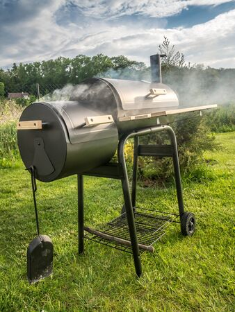 bower: Barbeque meal being prepared using black grill with chimney in the backyard Stock Photo