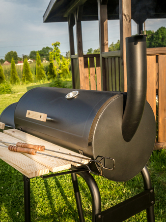 bower: Black grill with chimney with wooden summer house in the background Stock Photo