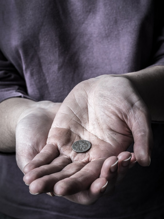 Closeup of poor begging woman hands holding a coin Stock Photo