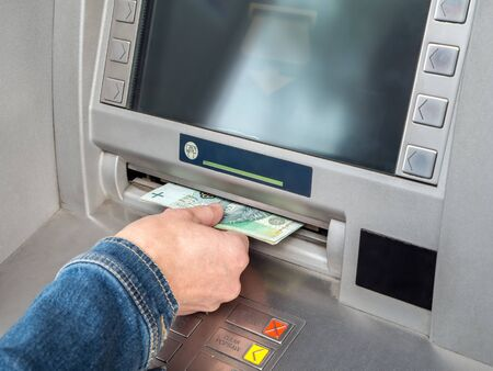 withdraw: Closeup of womans hand withdrawing cash from ATM slot Stock Photo