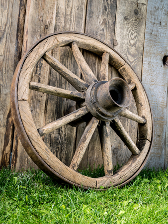 Old wooden wagon wheel resting against rustic wooden fence Stock Photo