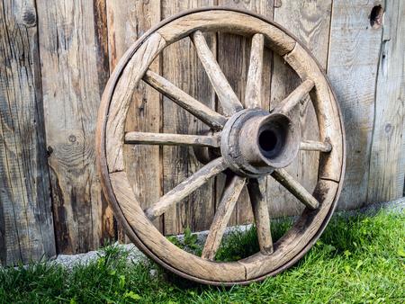 Old wooden wagon wheel resting against rustic wooden fence Standard-Bild