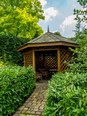 arbor: Wooden summer house surrounded by green shrubs and trees