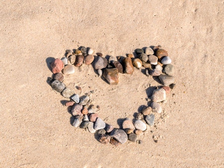 longing: Heart sign arranged from pebbles on beach sand