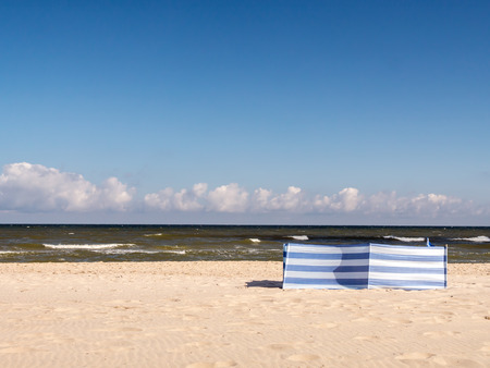 baffle: White and blue striped windbreak at the beach