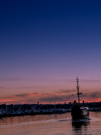 Old historical sail ship entering the marina against the sunset sky