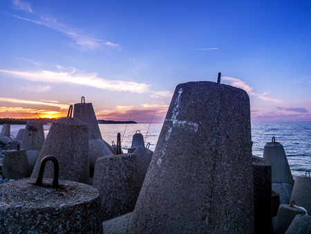 breakers: Massive concrete breakers stacked on the coastline against the sunset sky