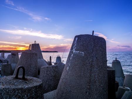 bulwark: Massive concrete breakers stacked on the coastline against the sunset sky