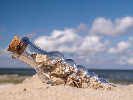 corked: Corked bottle with seashells stuck in the sand on the beach Stock Photo