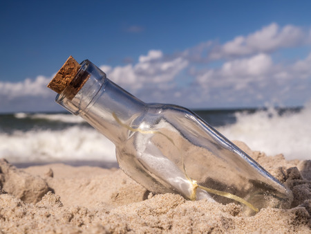 corked: Corked bottle with message stuck in the sand on the beach