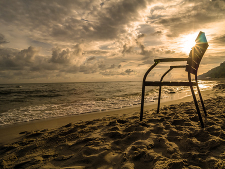 horison: Silhouette of wooden armchair against the rising sun at the beach
