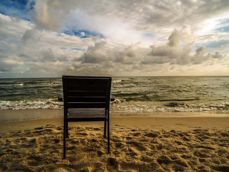 horison: Wooden armchair placed on the beach with the view to the sea